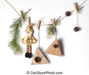 Decorative decoration for Christmas and New Year. Gifts, a toy snowman, pine branches, cones are attached to the rope with clothespins. Eco-friendly holiday concept. White background and place for an inscription