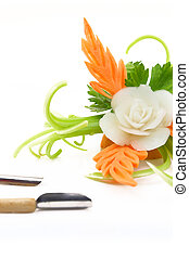 Decorative flower carved from vegetables with carving knives isolated