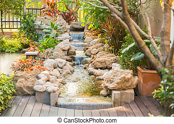 garden with a small steam and tree and stone