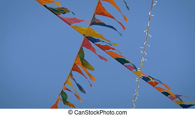 Decorative garland of multicolor flags waving in the wind at outdoor city festival, carnival, amusement park. Evening time, low light warm illumination. Holiday, celebration and anniversary concept