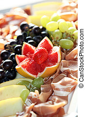 Decorative grapefruit and grape garnish on a meat platter prepared for a buffet at a wedding reception