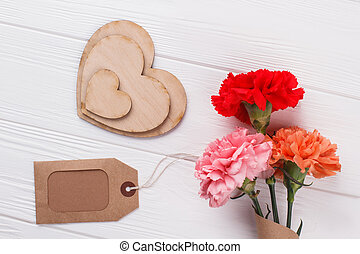 Decorative heart shaped wood, tag and colorful flowers.