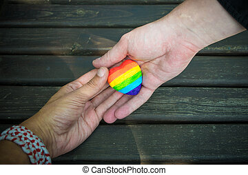 Decorative Heart with rainbow stripes in male hands. LGBT pride flag, symbol of lesbian, gay, bisexual, transgender for social movements. Homosexual love, Human rights concept. Copy space.