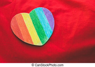 Decorative Heart with rainbow stripes on red background. LGBT pride flag, symbol of lesbian, gay, bisexual, transgender. Homosexual love, Human rights concept. Copy space.
