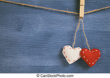decorative hearts hanging on the rope against blue wood wall