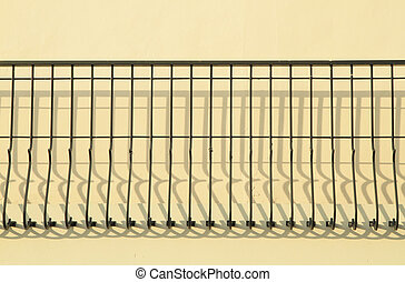 Decorative metal fence with shadow on the wall