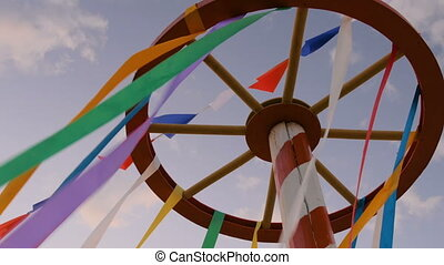 Decorative multicolor ribbons on wooden wheel construction at city street holiday, festival or carnival. City festival concept