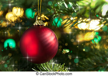 Decorative red bauble in a Christmas tree in front of a glitter background