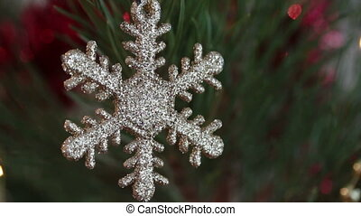 decorative snowflake on christmas tree decorated with flashing garlands