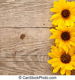 Decorative sunflowers on wooden background top view