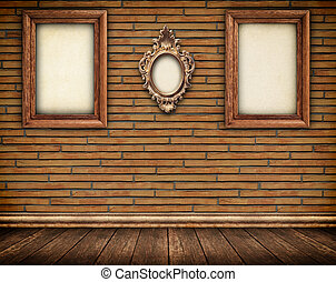 Three old frames on brick wall and wooden floor with skirting board.
