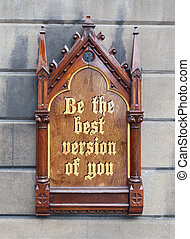 Decorative wooden sign hanging on a concrete wall - Be the best version of you