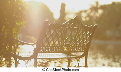 Decorative wrought iron bench on shore of a pond at sunset....