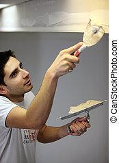 Decorator carefully plastering roof