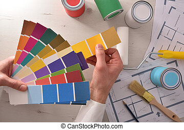 Decorator choosing a color for interior housing project top view