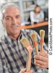 Decorator holding paint brushes