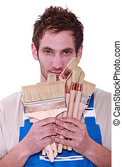 Decorator holding selection of paint brushes