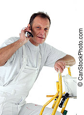 Decorator making a phone call whilst up a ladder
