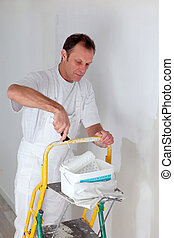 Decorator painting a room white with a roller