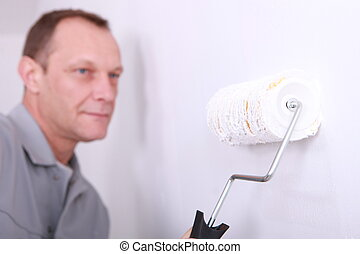 Decorator painting a room white with the roller in the foreground
