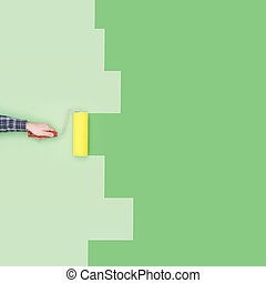 Decorator painting a wall with a paint roller