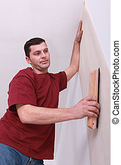 Decorator smoothing down wallpaper with a brush