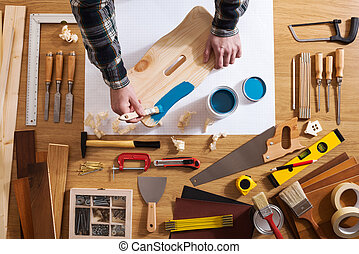 Decorator varnishing a wooden stool with a blue coating on a work table with DIY tools all around, top view