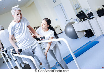 Dedicated aged man trying to walk on a treadmill and looking optimistic