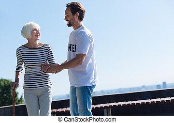 Dedicated gallant man taking positive senior lady on a stroll