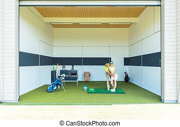 Dedicated golf coach using modern equipment while teaching a young woman