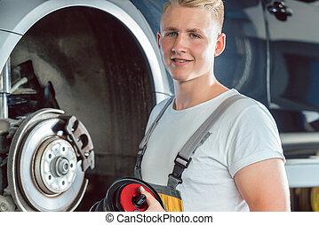 Dedicated mechanic working in a modern automobile repair...