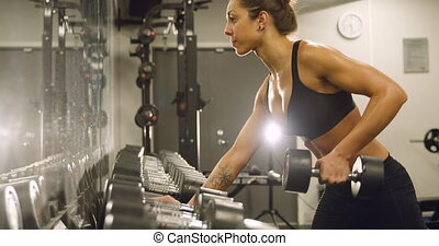 Dedicated woman training and lifting weights in fitness gym...