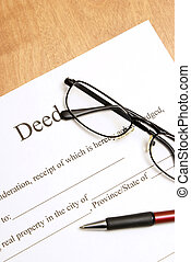 Deed Papers - A closeup shot of deed papers and glasses to...