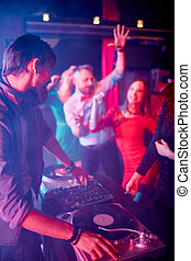 Deejay at disco - Male deejay adjusting sound with group of...