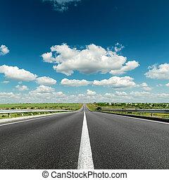 deep blue cloudy sky over asphalt road
