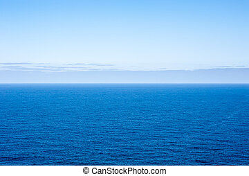 Deep blue empty ocean seascape with clouds on horizon -...