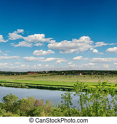 deep blue sky and river in green