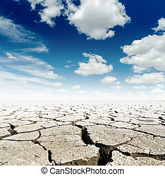 deep blue sky with clouds over drought earth with cracks
