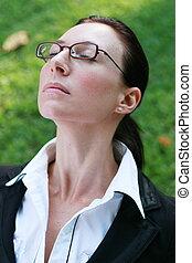 deep breath - an elegant woman taking a deep breath in park