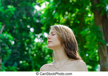 deep breath - a girl taking a deep breath in the green park