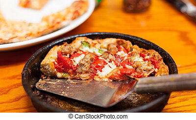 Wooden table with deep-dish personal pizza with serving knive and other meals