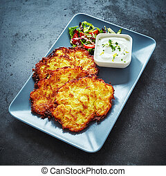 Deep fried German potato fritters with creamy dip served on ...