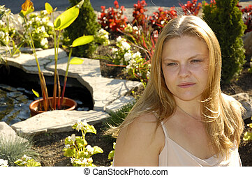 Deep in Thought - Attractive Blond Young Woman in a Garden