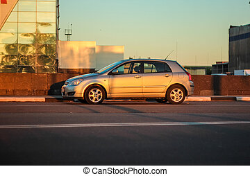 Deep morning dawn with highlights in the orange rays of the summer sun on the road against the background of industrial structure on a blurred background in the light and car