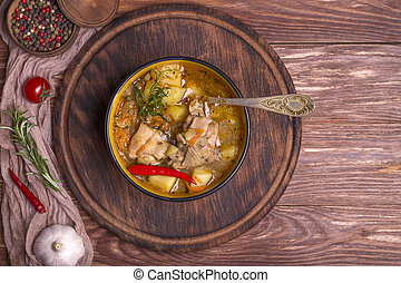 Deep plate with stewed potatoes and chicken meat on a wooden table. Top view, copy space