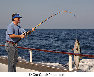 Deep Sea Fishing - Man fishing from the edge of a moving...