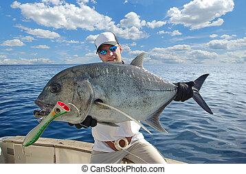 Happy fisherman holding a beautiful trevally fish. Deep sea fishing, big game fishing, catch of fish. popping fishing