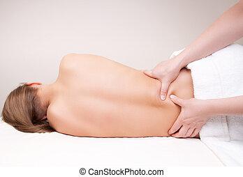 Deep tissue massage on the woman's lower back on quadratus ...