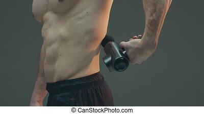 Deep tissue percussion massager, athletic guy massaging lower back for pain relief on gray studio background. High quality 4k footage
