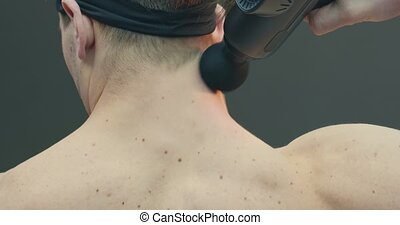 Deep tissue percussion massager, sports guy massaging neck for pain relief on gray studio background, back view. High quality 4k footage